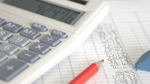 Calculator, pencil and eraser laying on list of figures, close-up
